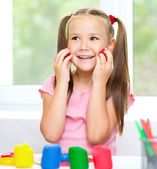 Girl is having fun while playing with plasticine