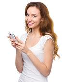 junge Frau tippt SMS auf ihr Handy