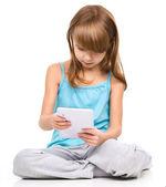 mladá dívka je pomocí tabletu