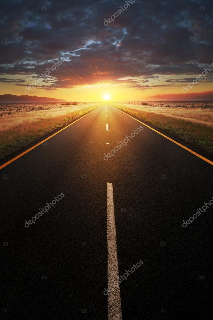 Straight asphalt road leading into sunlight