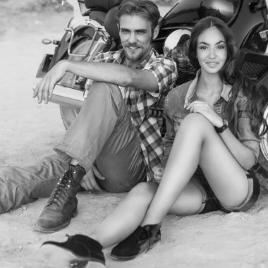 Two people and bike - fashion woman and man sitting by motorbike