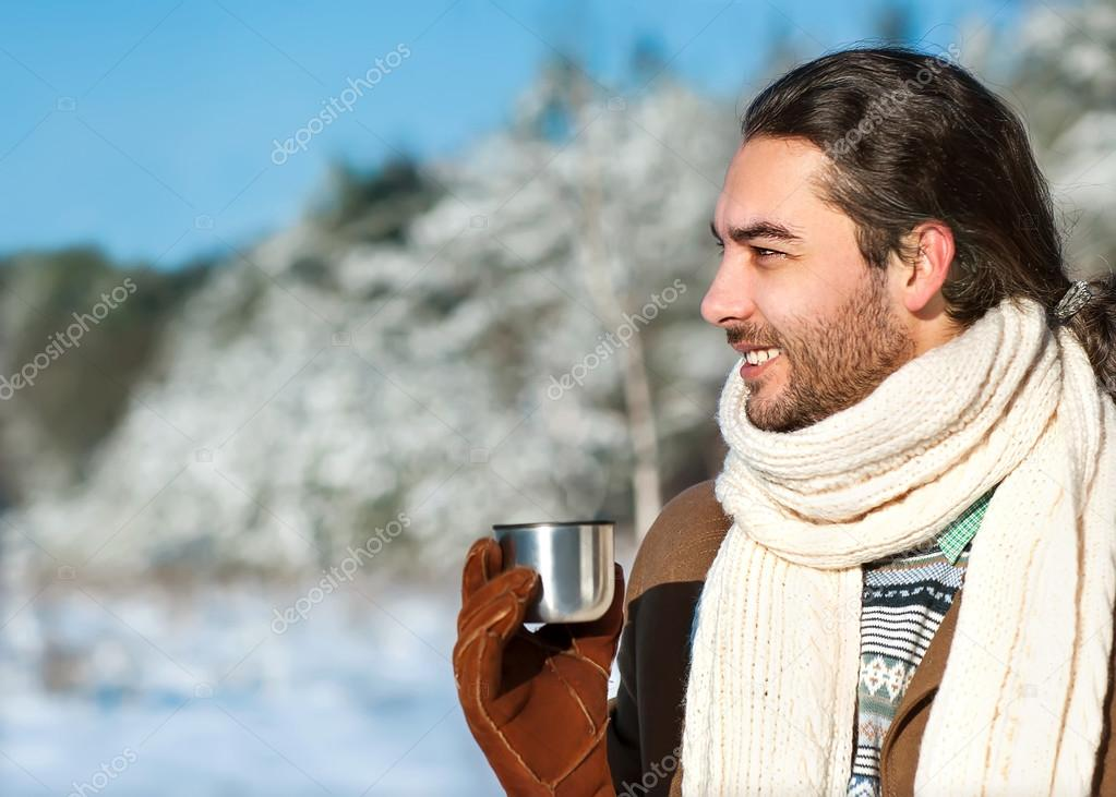 young man with tea standing in snowy woods
