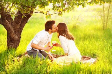 Couple in love kissing in nature are holding wine glasses
