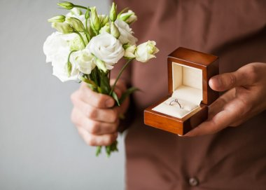 Happy man holding an engagement ring box