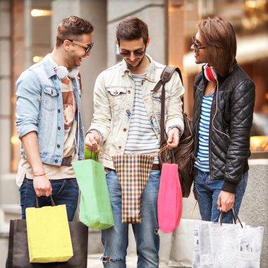 Three Young male fashion metraseksuals shop. Men shopping walk.