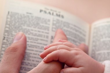 Baby Holding Dad Finger on Bible