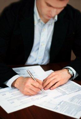 Business men filling out documents on a desk.