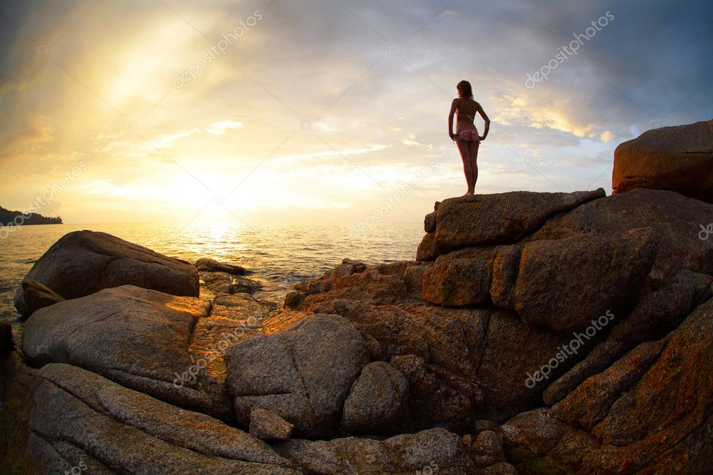 Woman standing on a rock and looking to the horizon over sea