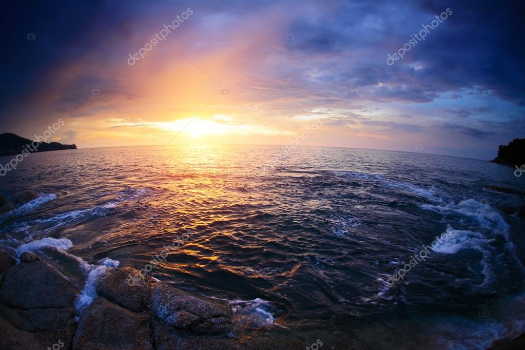 Rocky coast sea with waves at sunset