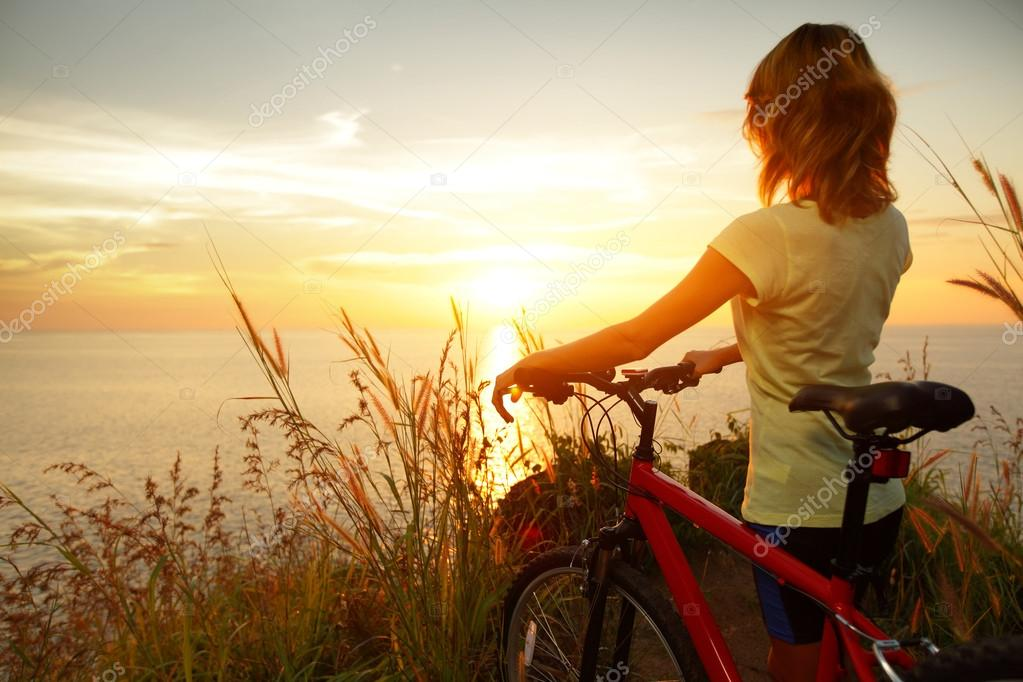 Young lady standing with bicycle