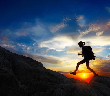 Hiker with backpack jumping over rocks with sunset sky on the background stock vector