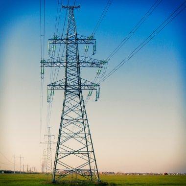 Electricity pylon against blue cloudy sky. Vintage
