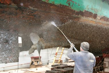 Work in dry dock with water jet cleans the bottom of the ship fr
