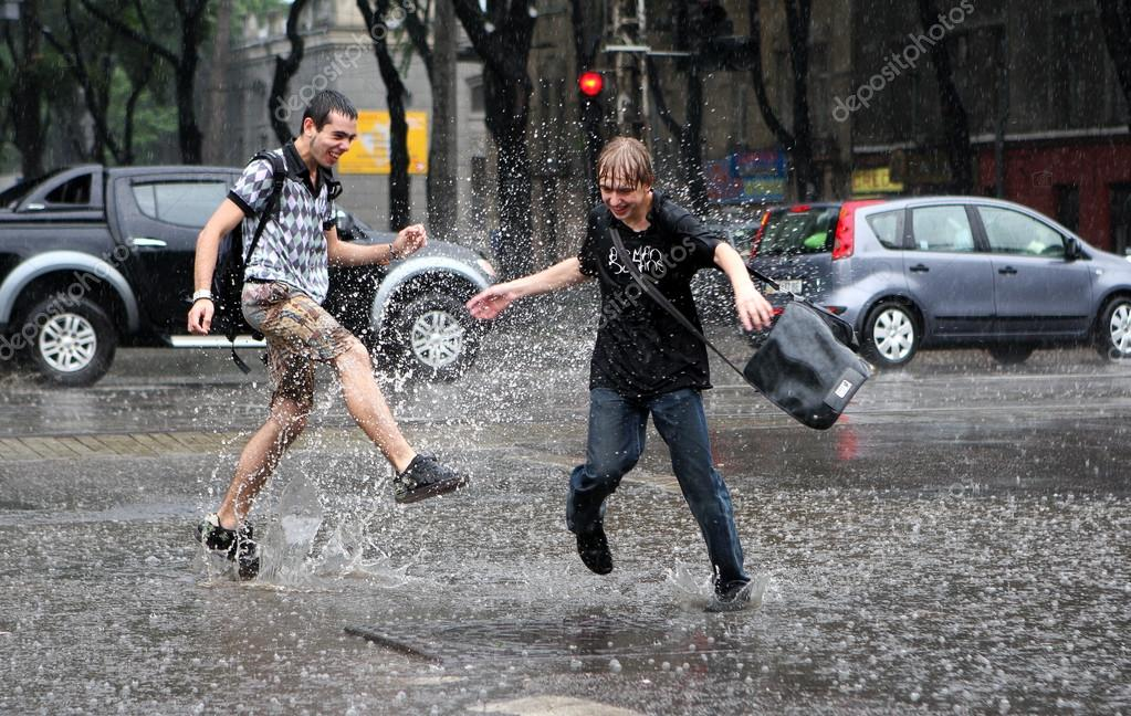 ODESSA, UKRAINE - JUNE 21: Two boys spray water in the puddles i