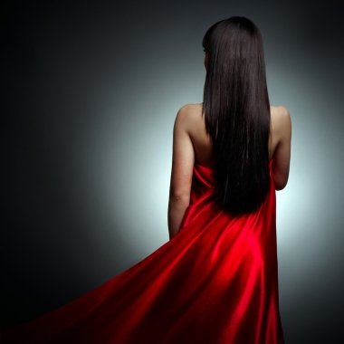 Beautiful girl in red dress back on black background