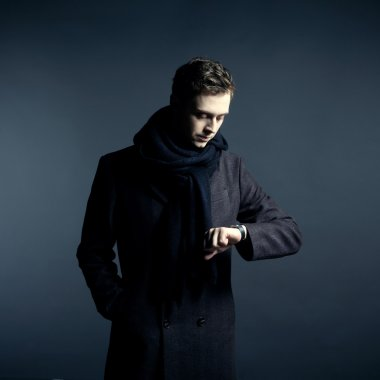 Portrait of handsome stylish man in coat with watch