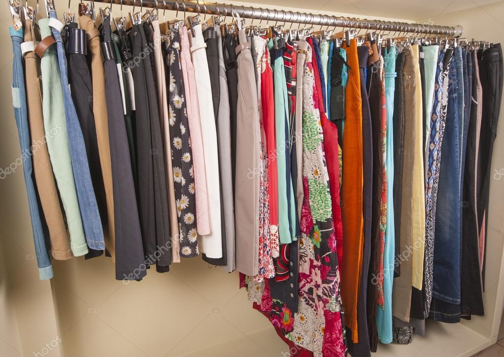 18dd06f8f8f3 Ποικιλία από πολύχρωμα γυναικείων ενδυμάτων που κρέμονται σε ράγα στο  κατάστημα μόδας — Εικόνα από paulvinten