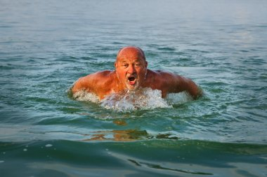 Swimmer. Senior man swimming butterfly strokes. Caucasian male aged 60 years.