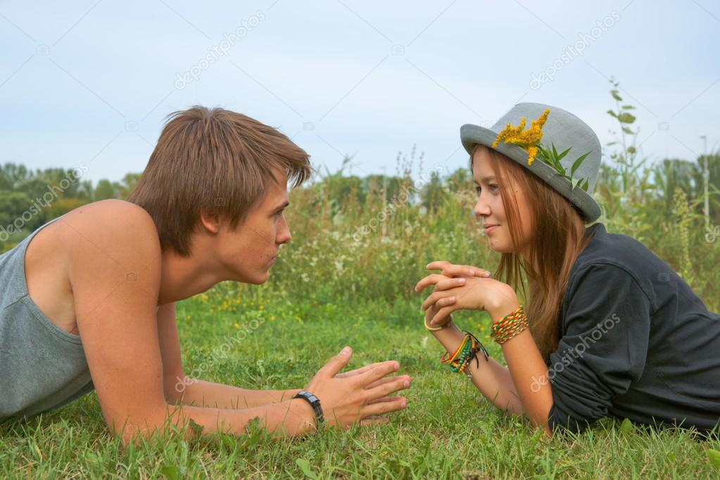 Boy and girl, teenagers lying on the grass and looking into each others eyes