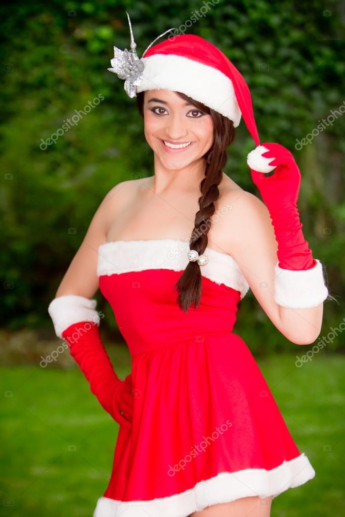 f37bcce6549a Beautiful young woman in santa suit on the summer garden — Photo by ...