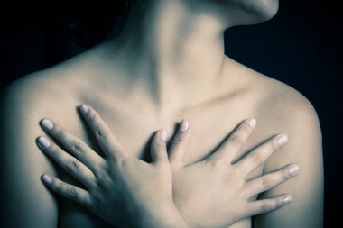 Close up, topless woman body covering her breasts