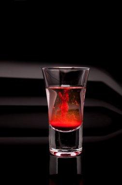 Red shot glass on a dark background
