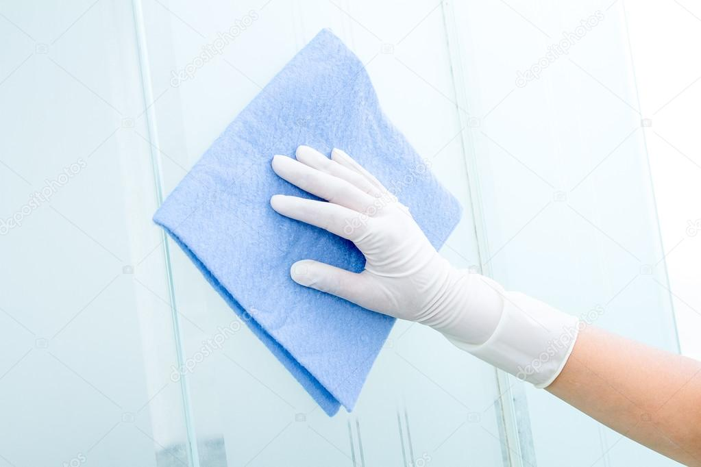 Hand and glove with blue sponge cleaning glass