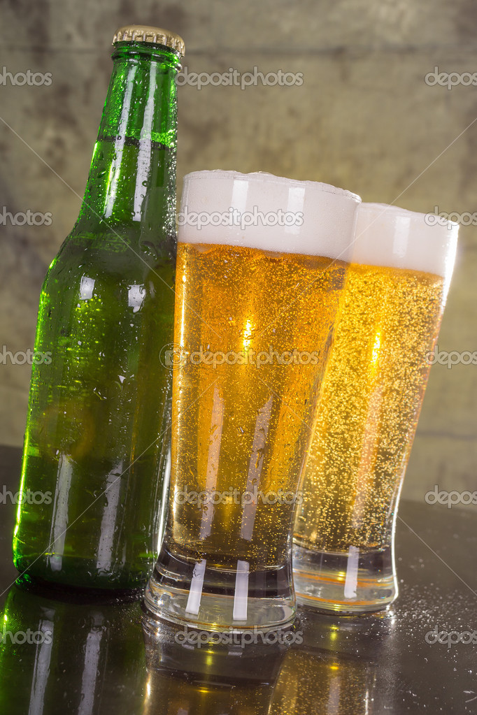 Glasses of beer with green bottle