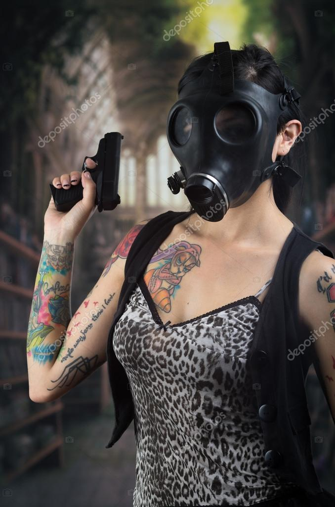 Woman with gas mask and gun in a grunge background