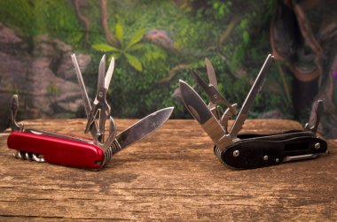 Several swiss army knifes on wood in the rainforest