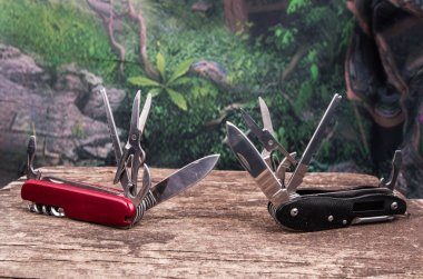 Several swiss army knifes on wood the rainforest