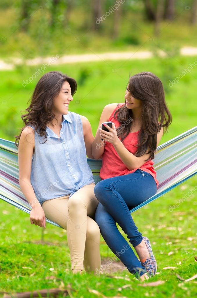 Two young girls resting on a hammock smiling