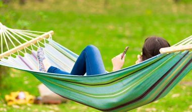 young girl lying on a hammock with cell phone