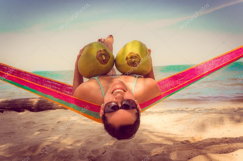 Beautiful young girl lying in a hammock holding two coconuts