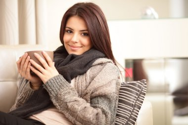 Happy young woman sitting on sofa in cosy cloths with cup of cof