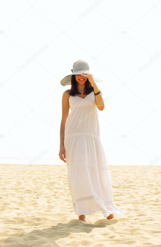 dc4048f8eb813 Mujer de pie en la playa de vestido blanco con un sombrero cubriendo sus  ojos —
