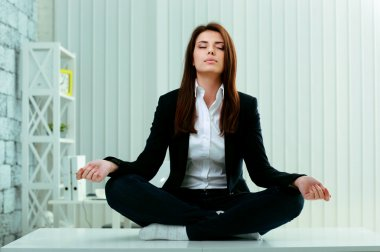 Businesswoman meditates on the table