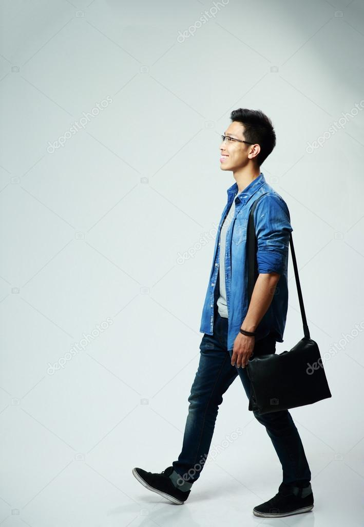 33b0b4aeb450 Studio shot of a young asian man walking on gray background — Photo by  Vadymvdrobot