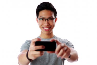 Happy asian man taking photo with smartphone over white background stock vector