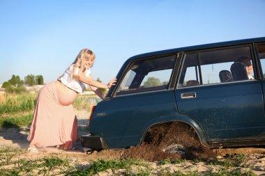 Pregnant woman pushing car