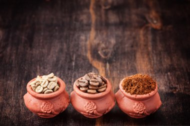Green coffee, ground coffee, roasted coffee beans. Different types of coffee on wooden background
