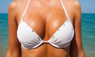Beautiful large female breasts in a white swimsuit.