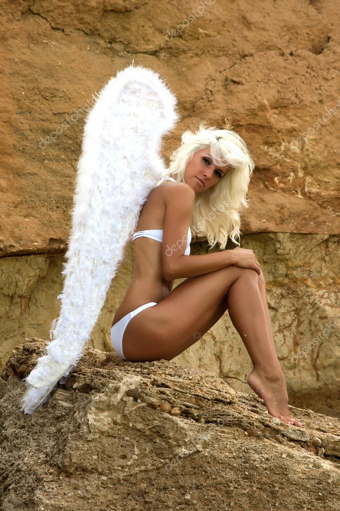 Beautiful blonde model with a perfect body and angel wings lies on a white background stock image