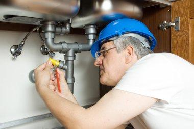 Senior Plumber repairing water boiler