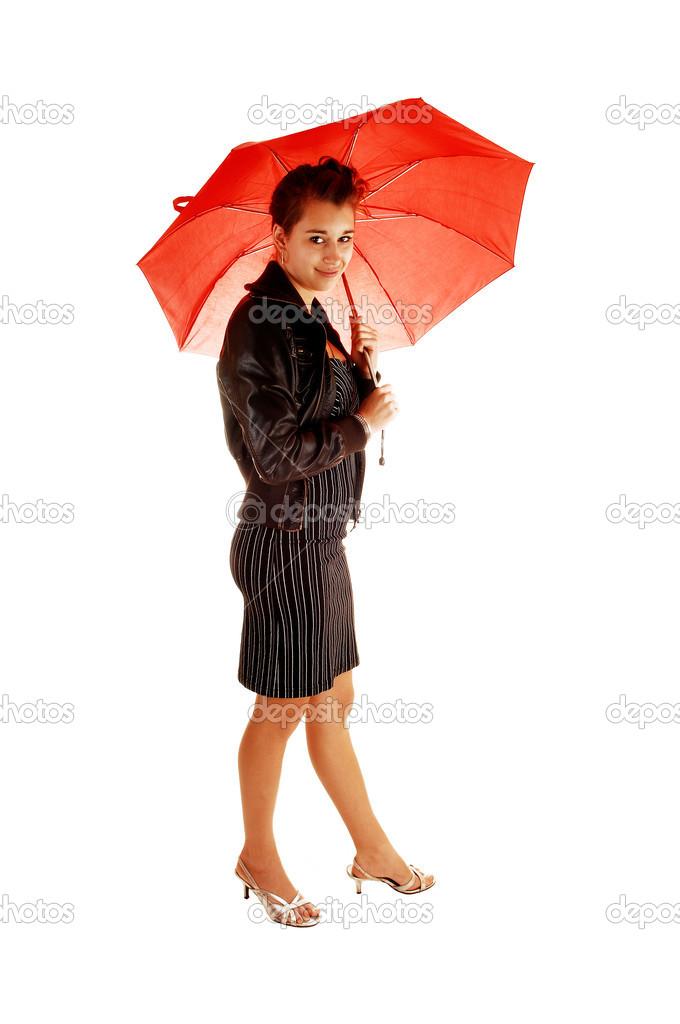 d1acd23233e2 Una bella giovane donna in un abito nero e giacca di pelle marrone e tacchi  alti in piedi sfondo bianco tenendo un ombrello rosso nella Fronda di lei —  Foto ...