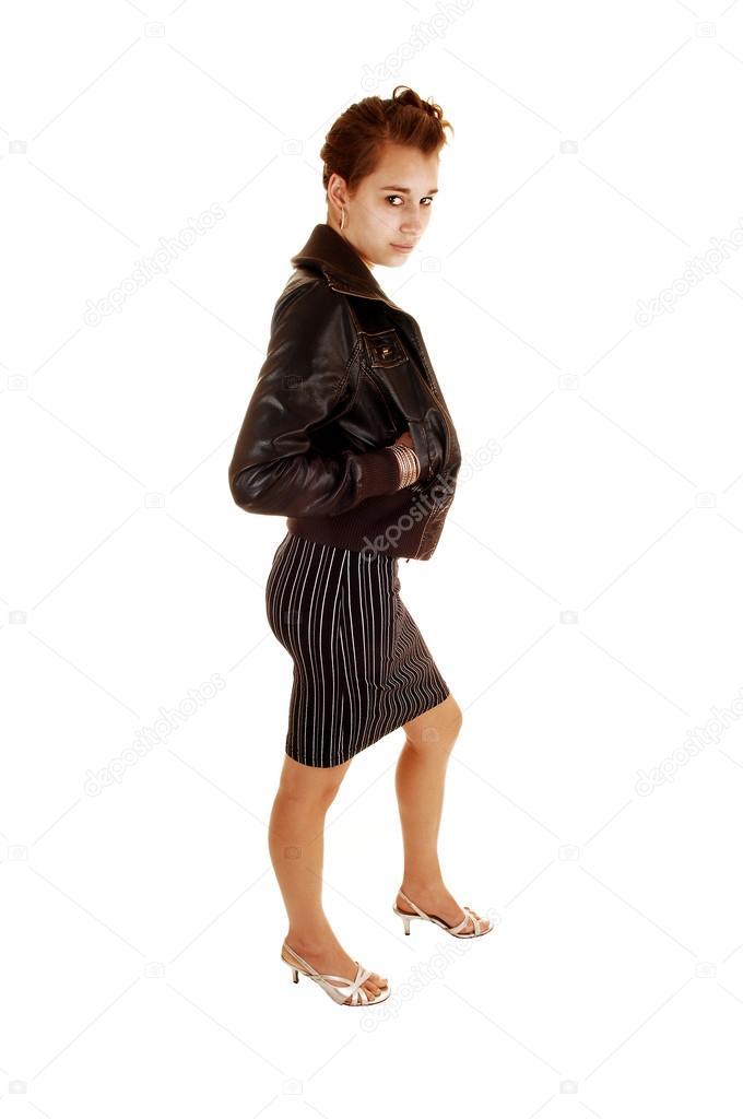 fd3ce1c98c25 Una donna abbastanza giovane in piedi per sfondo bianco in un abito a righe  nero tacchi alti e una giacca di pelle marrone