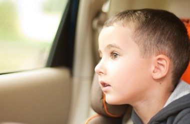 Curious little boy in the car watching the window