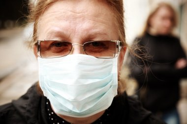 woman protecting herself against influenza with a face mask