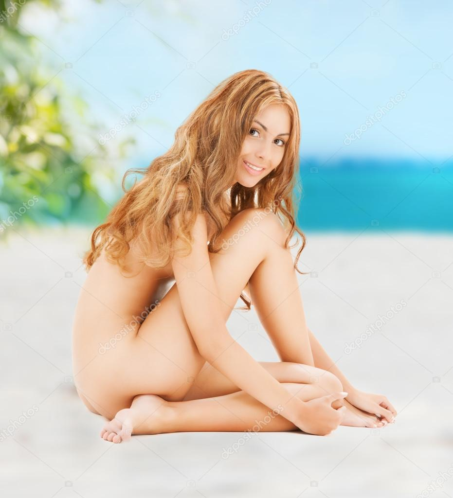 naked woman with long hair sitting on the beach — stock photo