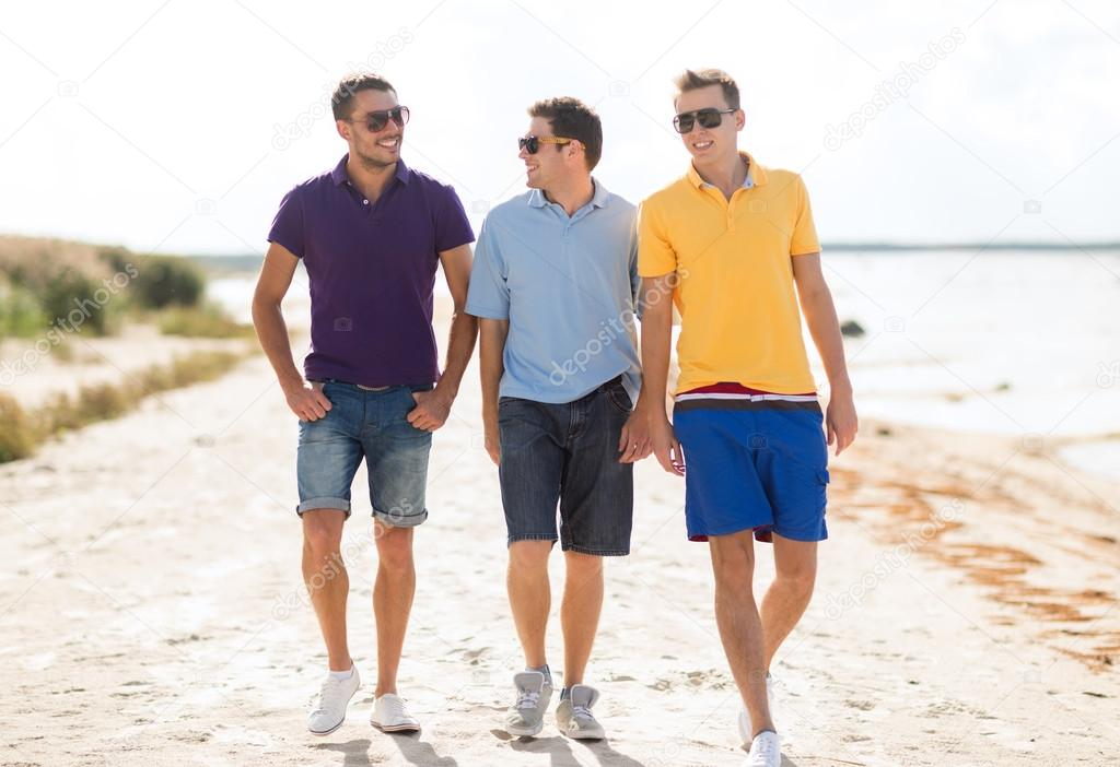 group of friends walking on the beach stock photo